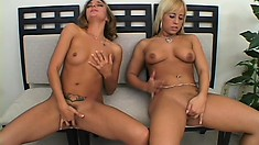 Two adorable lesbians sit side by side and finger their shaved pussies to orgasm