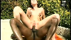With the sun on her body, a sexy brunette has a black stud fucking her tight pussy