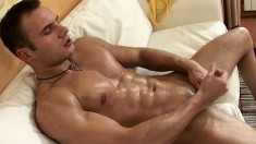 Nick spreads his body across the hotel bed and strokes his long dick